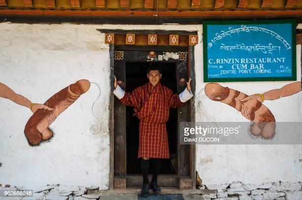 Homme se tenant sur le seuil de l'entree d'un restaurant mur decore avec des penis peints le 11 mars 2013 Village de Nobding Bhoutan