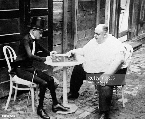 L'Homme Squelette et le Martyr de l'Obèse tous deux personnages d'un cirque londonien jouent aux dames pendant leurs loisirs le 7 juillet 1931