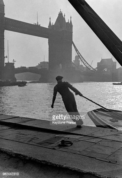 Homme tirant une amarre sur les docks à Londres en Angleterre au RoyaumeUni en 1936 En arrièreplan le Tower Bridge