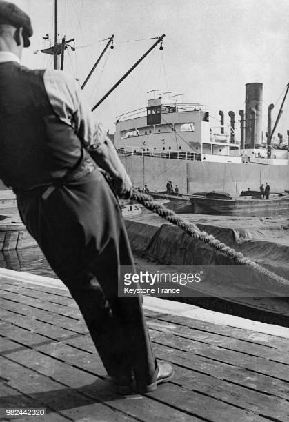 Homme tirant une amarre sur les docks à Londres en Angleterre au RoyaumeUni en 1936