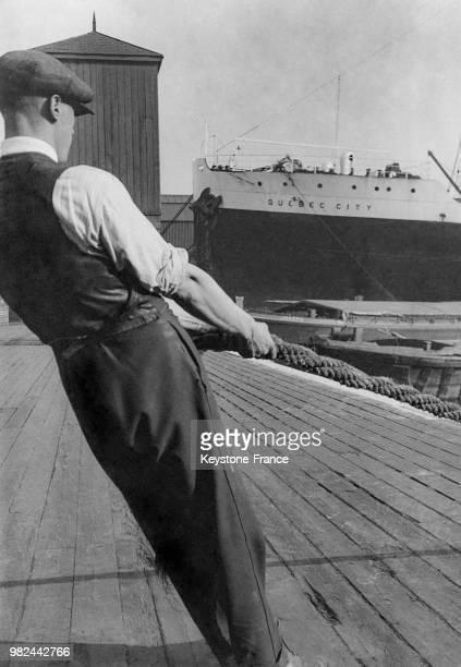 Homme tirant une amarre sur les docks à Londres en Angleterre au RoyaumeUni en 1936 En arrièreplan le navire 'Quebec City'