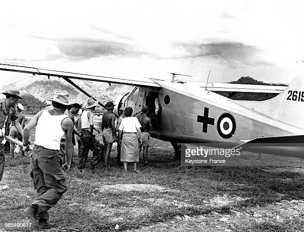 Hommes et femmes du service de santé viennent chercher les blessés de Diên Biên Phu à la porte de l'avion avec des brancards au Viêt Nam en 1954