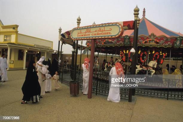 Hommes et femmes en costume traditionnel à côté d'un manège dans le Parc d'attraction de l'an 2000 à Koweit City en mai 1984 au Koweit