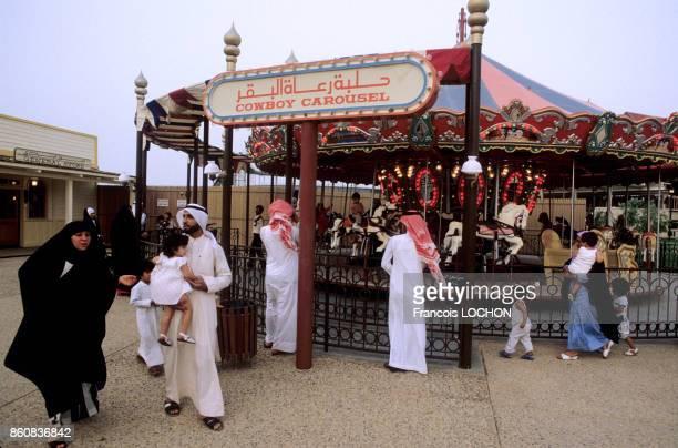 Hommes et femmes en costume traditionnel à côté d'un manège dans le parc d'attractions de l'an 2000 à Koweït City en mai 1984 Koweït