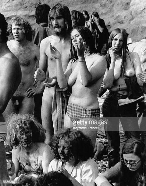Hommes et femmes hippies seins nus ou totalement nus écoutant la musique sur la plage lors du festival de l'Ile de Wight RoyaumeUni le 31 août 1970