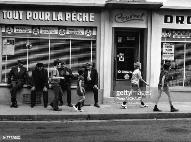 Hommes âgés assis devant une droguerie en France