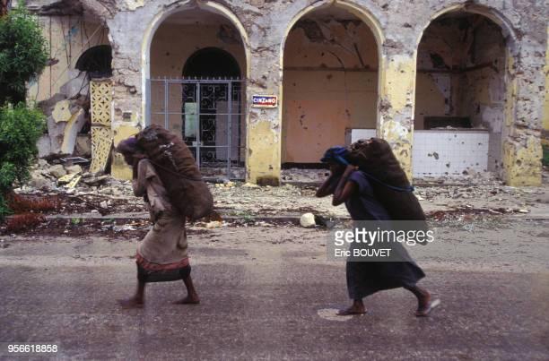 Hommes transportant des sacs de vivres en juillet 1992 à Mogadiscio en Somalie