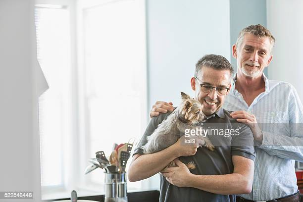 Homosexual couple at home with pet dog