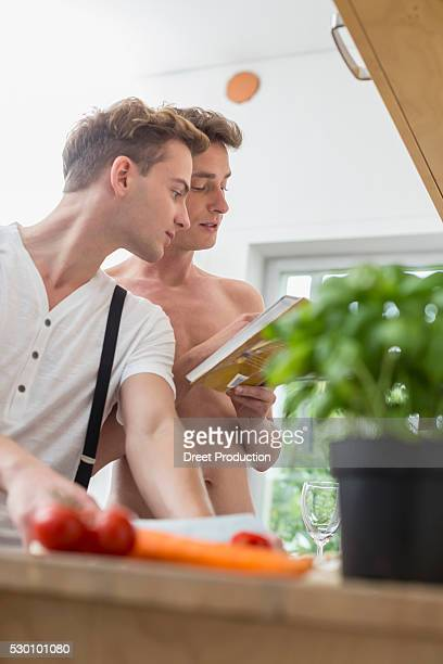 Homosexual couple cooking food in kitchen
