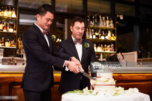 Homosexual couple cutting the wedding cake at the reception dinner.