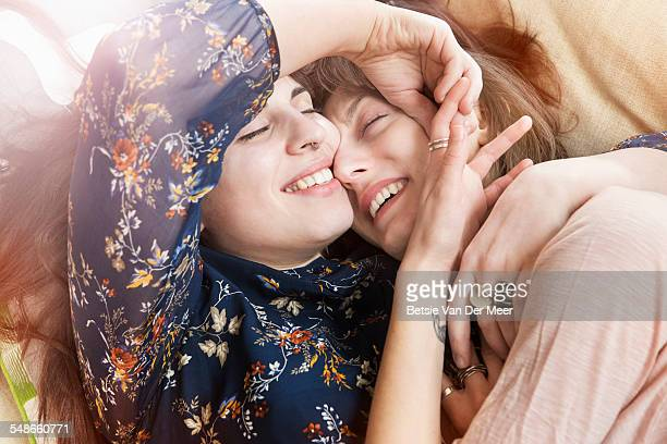 homosexual couple embracing, laying on sofa. - lesbian stock pictures, royalty-free photos & images