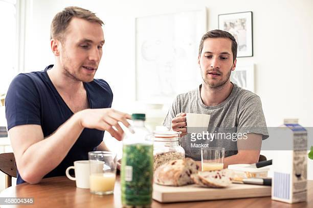 Homosexual couple having breakfast together at table in home