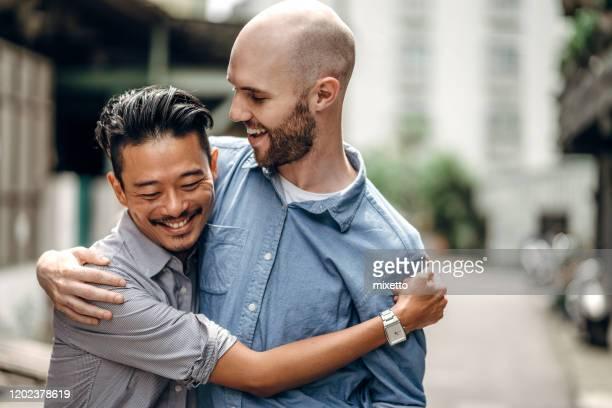 市内の同性愛者のカップル - ゲイ ストックフォトと画像