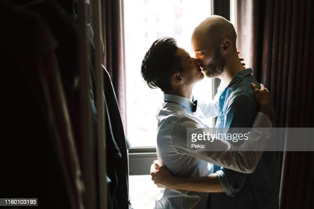couples homosexuels embrassant à l'appartement - embrasser sur la bouche photos et images de collection