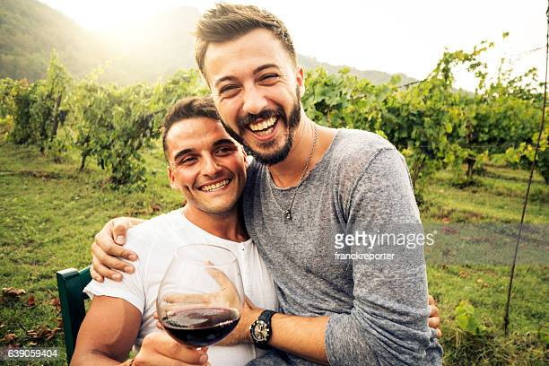 homosexual couple kissing at dusk drinking wine