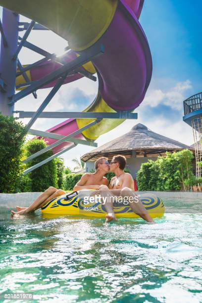 Homosexual couple - men - having fun in waterpark
