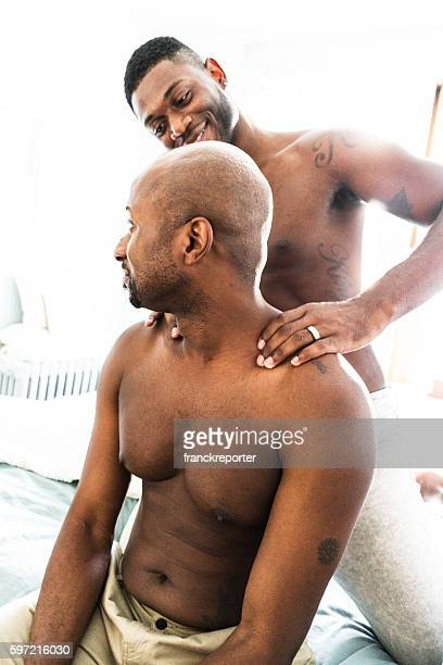 homosexual couple relaxing togetherness and sharing a massage - black massage therapist stock photos and pictures