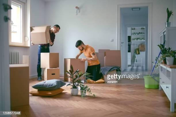 casal homossexual desempacotar caixas em uma nova casa - on the move - fotografias e filmes do acervo