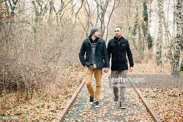 homosexual couple walking through the autumn forest, holding hands