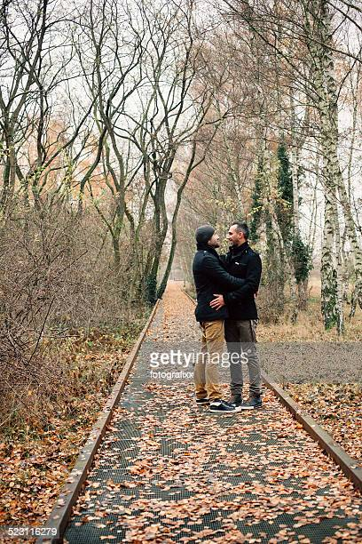homosexual couple walking through the autumn forest - human relationship stock pictures, royalty-free photos & images