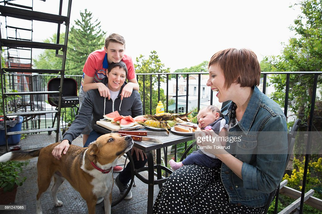 Homosexual couple with children having lunch : Stock Photo