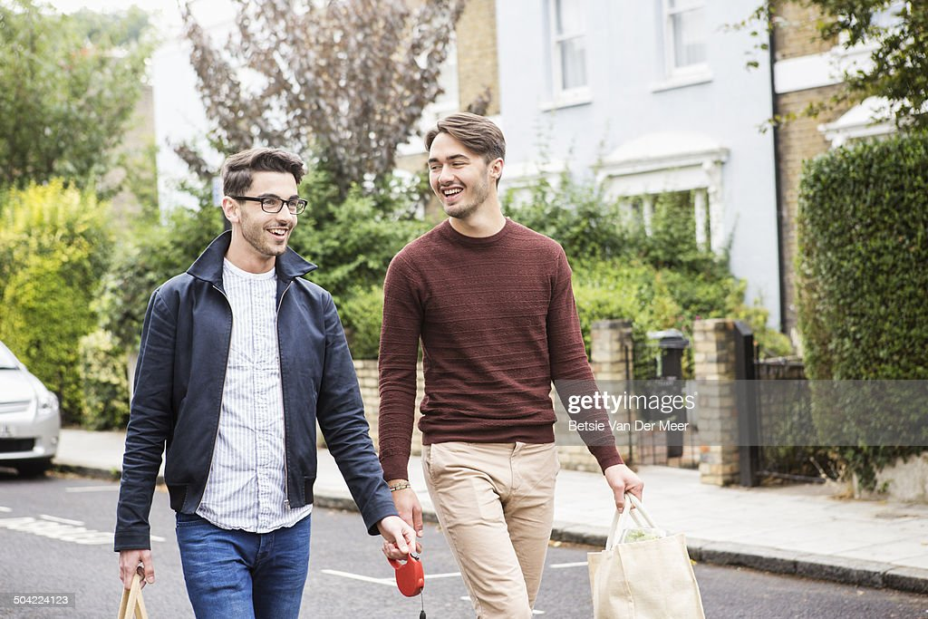 homosexual couple with shopping walking on street. : Stock Photo
