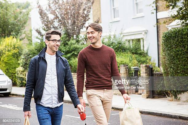 homosexual couple with shopping walking on street. - commerciële activiteit stockfoto's en -beelden