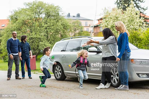 Homosexual families enjoying by car on street