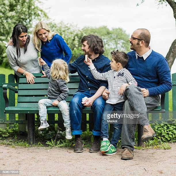 homosexual families spending leisure time in park - couple chocolate stock pictures, royalty-free photos & images