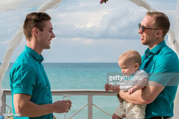 homosexual godparents and their young nephew in a wedding celebration - godfather godparent stock pictures, royalty-free photos & images