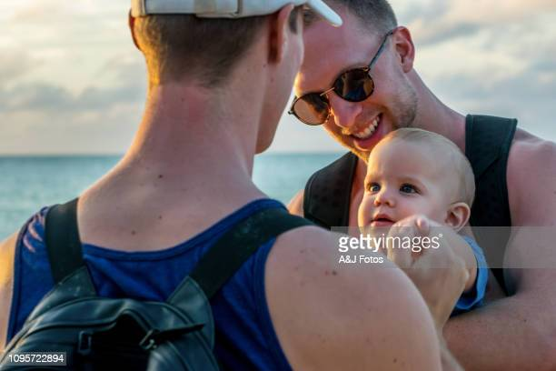 homosexual godparents and their young nephew - godfather godparent stock pictures, royalty-free photos & images