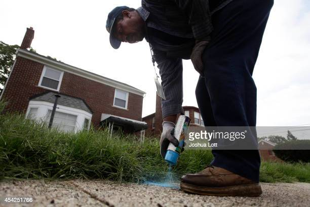Homrich worker spray paints a blue line to indicate that the water supply was turned off to a home August 27 2014 in Detroit Michigan The Detroit...