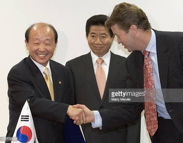 Hon David Culiffe Minister of Communications shakes hands with Mr Rho Junhyong Korean Minister of Information and Communication after signing a...