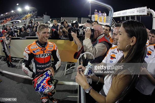 Honda MotoGP rider Casey Stoner of Australia celebrates with his wife Adriana after winning pole position during the qualifying practice session at...