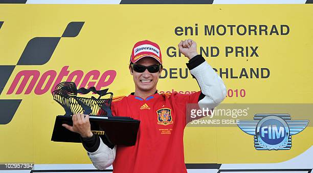 Honda MotoGP rider Dani Pedrosa of Spain holds up his trophy on the podium after his victory of the Moto Grand Prix of Germany at Sachsenring Circuit...