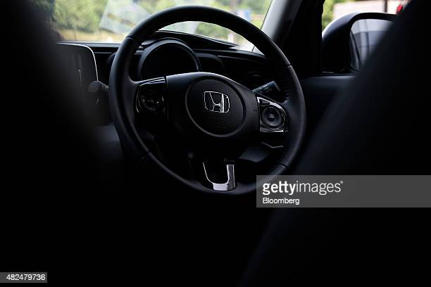 A Honda Motor Co badge and airbag unit for the driver's seat are seen on the steering wheel of the NOne Premium minicar in Tokyo Japan on Friday July...
