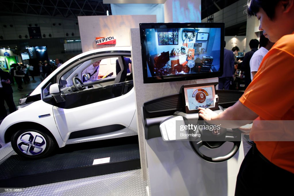 Exhibition Booth Assistant : A honda motor co booth assistant uses a tablet device to