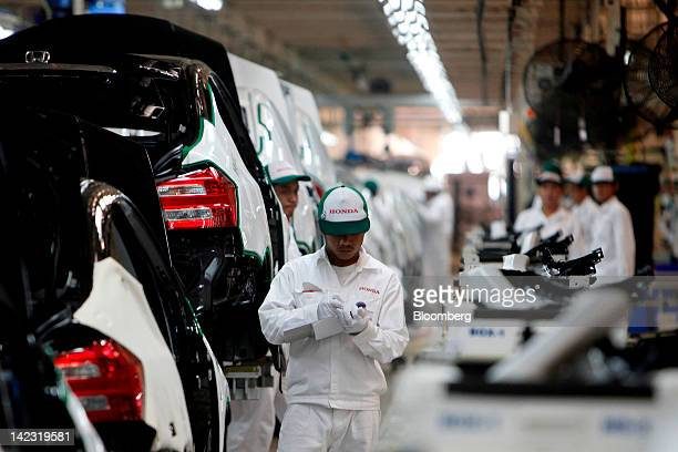 A Honda Motor Co employee performs inspections as he walks past Honda City vehicles on the production line at the company's assembly plant at the...