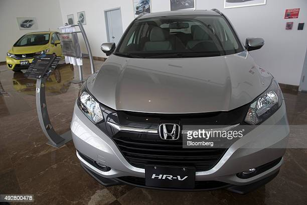 A Honda Motor Co HRV compact sport utility vehicle right and Fit subcompact vehicle sit on display at the main entrance of the company's transmission...