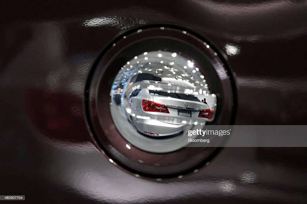 A Honda Motor Co Legend Hybrid Sedan Is Reflected On Gas Tank Door Of