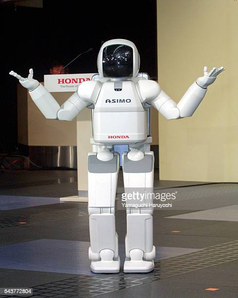 """Honda Motor Corp's humanoid robot """"ASIMO"""" raises its hands during a press preview in Tokyo. Honda Motor introduced a new, improved version of the..."""