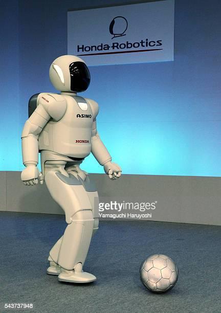 "Honda Motor Co.'s human robot ""Asimo"" kicks a soccer ball during a news conference at the company's research facility in Wako, near Tokyo, Tuesday,..."