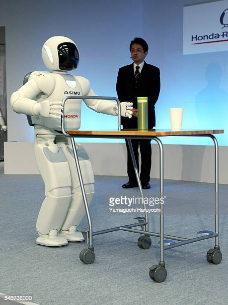 """Honda Motor Co.'s human robot """"Asimo"""" wheels a drink on a trolley during a news conference at the company's research facility in Wako, near Tokyo,..."""