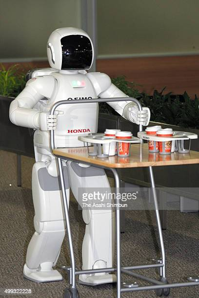 Honda Motor Co's humanoid robot 'ASIMO' carries a trolly at the company headquarters on December 11 2007 in Tokyo Japan