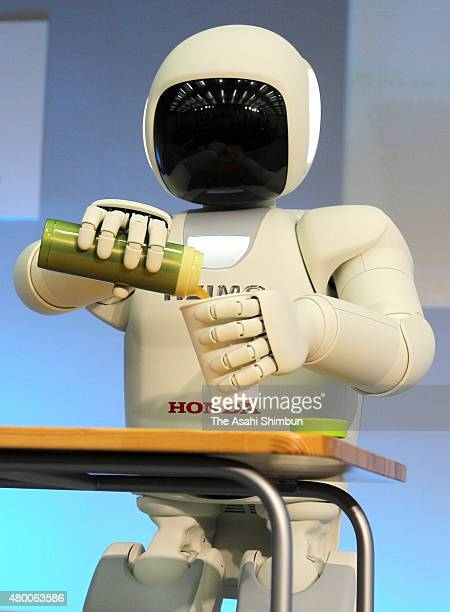 Honda Motor Co's humanoid robot ASIMO pours a water into a cup during the press briefing on robot technology on November 8 2011 in Wako Saitama Japan