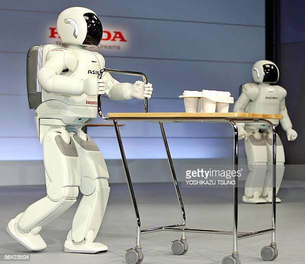 Honda Motor's new humanoid robot Asimo which can run at a speed of 6 kph and also to run in a circular pattern pushes a drinks tray at the company's...