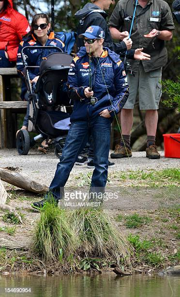 Honda rider Casey Stoner of Australia patiently waits to catch a trout as his wife Adriana looks on during a media event in the lead-up to the...