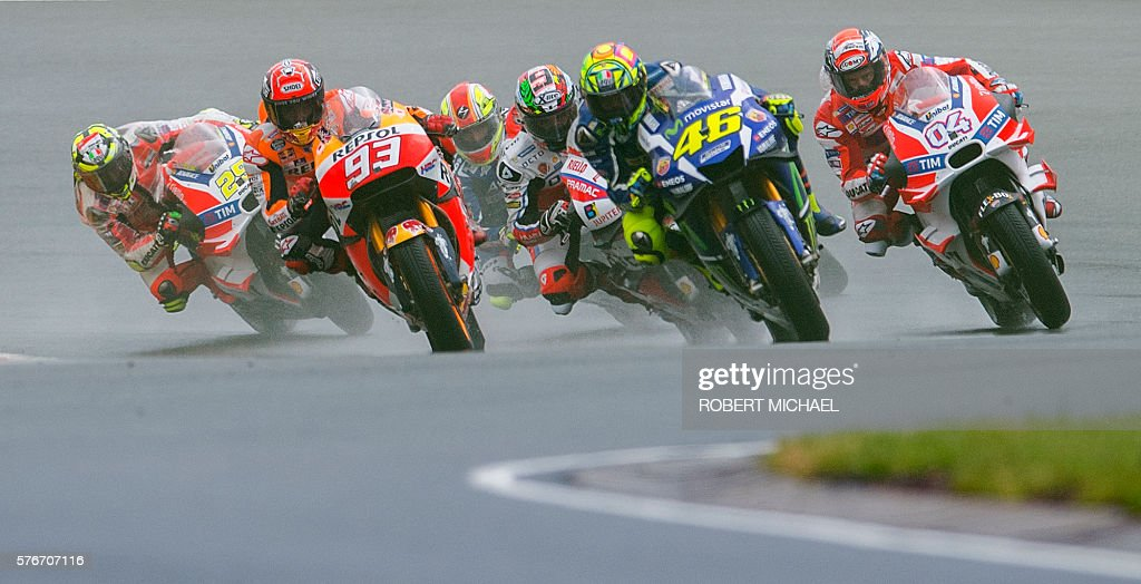 Honda rider Marc Marquez of Spain, Yamaha rider Valentino Rossi of Italy an Ducati rider Andrea Dovizioso of Italy lead the pack during the MotoGP race of the Grand Prix of Germany at the Sachsenring Circuit on July 17, 2016 in Hohenstein-Ernstthal, eastern Germany. / AFP / Robert MICHAEL