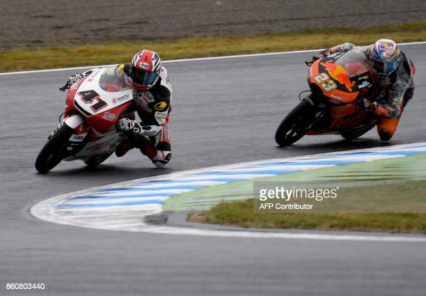 Honda rider Nakarin Atiratphuvap of Thailand leads KTM rider Niccolo Antoneli of Italy during the Moto3class second practice session of the MotoGP...