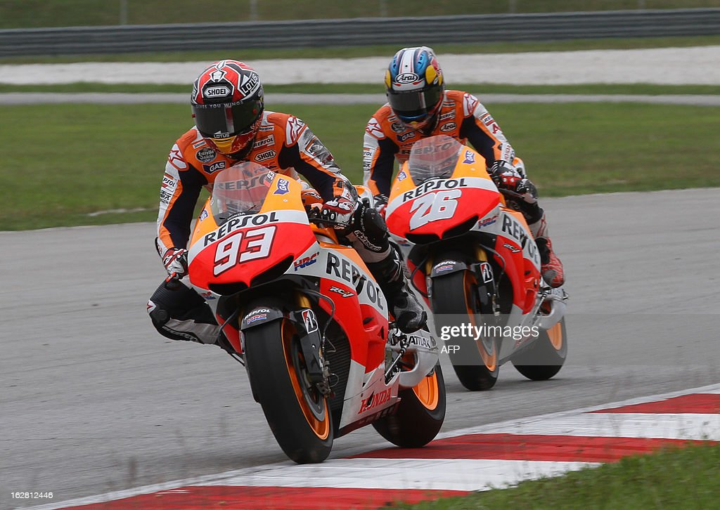 Honda riders Marc Marquez of Spain (L-#93) rides ahead of his teammate Dani Pedrosa of Spain (R) on the third day of the pre-season MotoGP test session at the Sepang circuit outside Kuala Lumpur on February 28, 2013. AFP PHOTO / Peter LIM